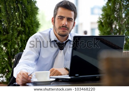Young handsome businessman working on laptop,  outdoor - stock photo