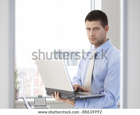 Young handsome businessman working on laptop, standing in bright office.?