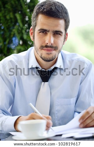 Young handsome businessman writing, outdoor