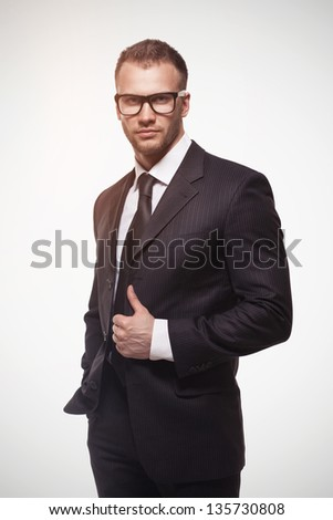 Young handsome businessmanman in black suit and glasses isolated on light grey background