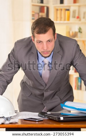 young handsome busy architect leaning on his desk working looking stressed