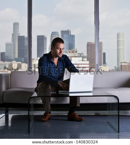 Young handsome casual business man working in a Penthouse Suite with Los Angeles Skyline behind him
