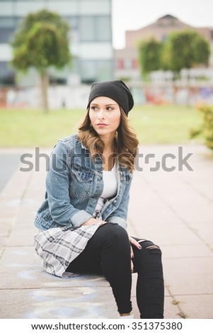 Young handsome caucasian blonde straight hair woman sitting on a small wall overlooking right, pensive - thoughtful, thinking future concept - stock photo