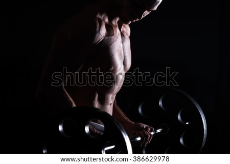 Young handsome caucasian bodybuilder sportsman working out with a barbell in gym, doing biceps training, close up - stock photo