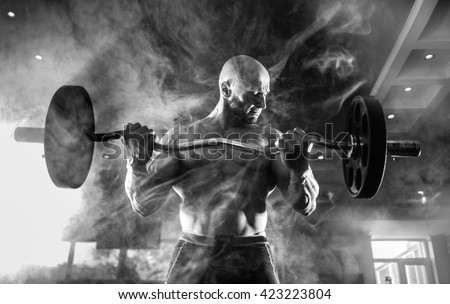 Young handsome caucasian bodybuilder sportsman working out with a barbell in gym, doing biceps training, smoke - stock photo