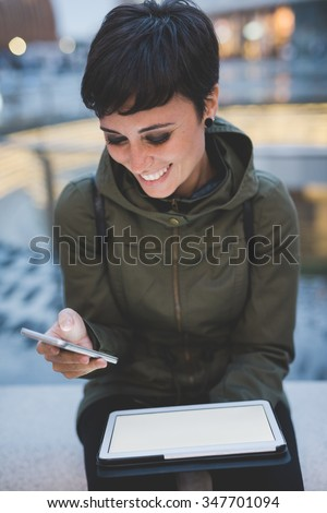 young handsome caucasian brown straight hair woman using smartphone and tablet, looking downward screen, smiling, face illuminated by screen light - multitasking, technology concept - stock photo