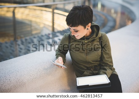 young handsome caucasian brown straight hair woman using smartphone and tablet, looking downward screen, smiling, face illuminated by screen light - multitasking, technology concept