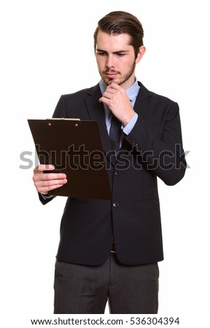 Young handsome Caucasian businessman reading clipboard while thinking