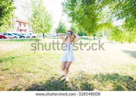young handsome caucasian long blonde straight hair hippy woman dancing in a city park, having fun, hands behind her head, touching hair - music, dance, happiness concept - stock photo