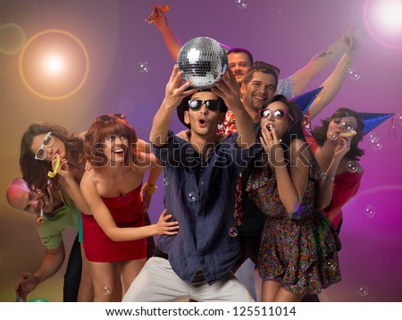 young handsome caucasian man holding a disco ball in his hands and looking at it amazed, with other happy people around him with party horns and hats, with colorfu lights in background - stock photo
