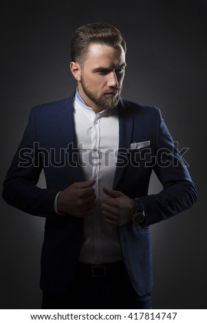 Young handsome caucasian man with perfect hairstyle wearing suit. Studio portrait on gradient black to grey background. Toned