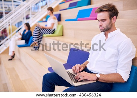 Young handsome caucasian man working on modern thin light laptop - stock photo