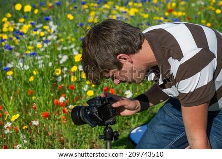 Young handsome caucasian photographer/videographer in botanic gardens