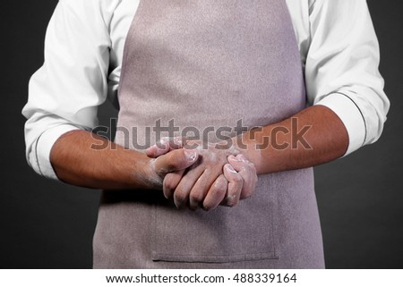 Young handsome chef cook with dirty hands, closeup