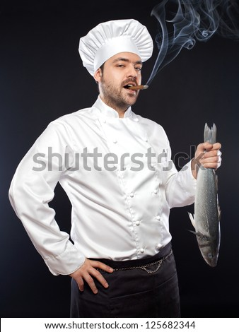 Young handsome chef with sea bass fish smoking cigar
