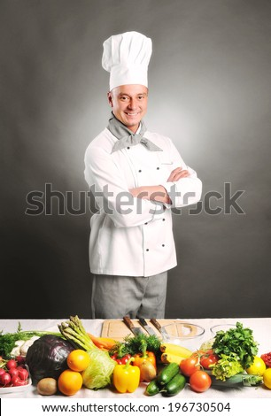 young handsome chef with vegetables isolated on white background - stock photo