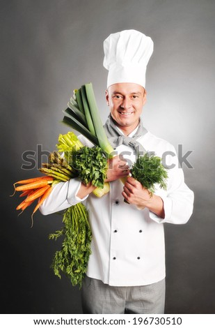 young handsome chef with vegetables on grey background - stock photo