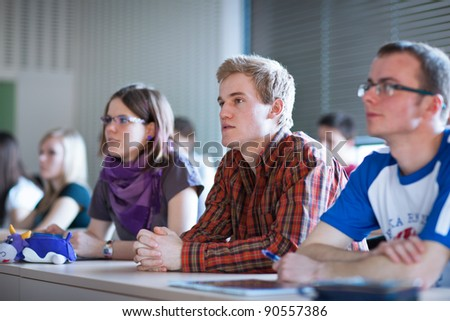 young, handsome college student sitting in a classroom full of students during class