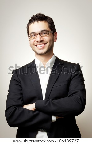 Young handsome confident man in black suit and glasses smiling