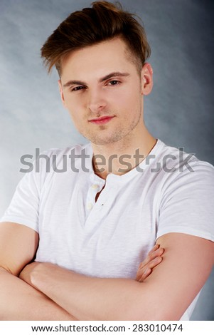 Young handsome confident man with folded arms.