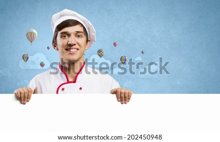 Young handsome cook holding white blank banner - stock photo