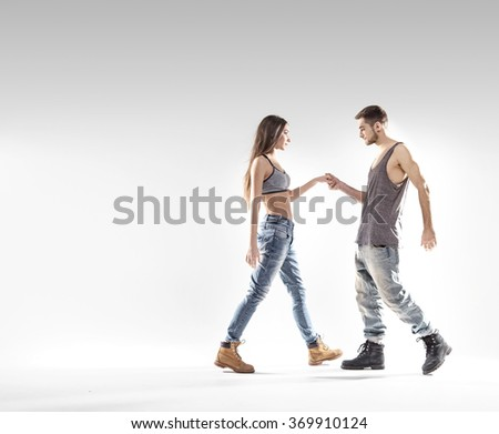 young handsome couple dancing hip-hop, studio background