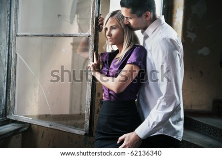 Young handsome couple looking at the window