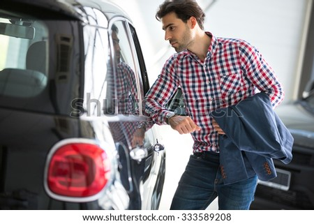 Young handsome customer in car showroom, watching  in car  - stock photo