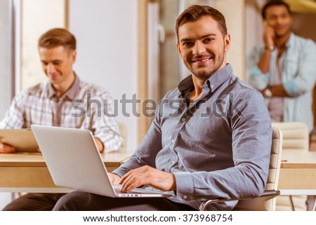 Young handsome dark-haired businessman in casual clothes smiling and using laptop, in the background two other businessmen working in office, using tablet and talking on the phone