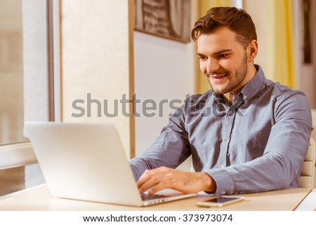 Young handsome dark-haired businessman in casual clothes smiling and using laptop while working in office - stock photo