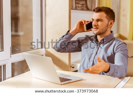 Young handsome dark-haired businessman in casual clothes talking on the phone and using laptop while working in office - stock photo