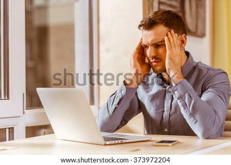 Young handsome dark-haired businessman in casual clothes using laptop and having headache while working in office - stock photo