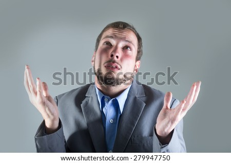 Young handsome desperate man, holding his hands open and looking up. - stock photo