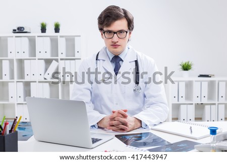 Young handsome doctor sitting at desk with laptop and x-rays in his office with plants on shelves in the background