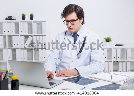 Young handsome doctor sitting at office desk and using laptop