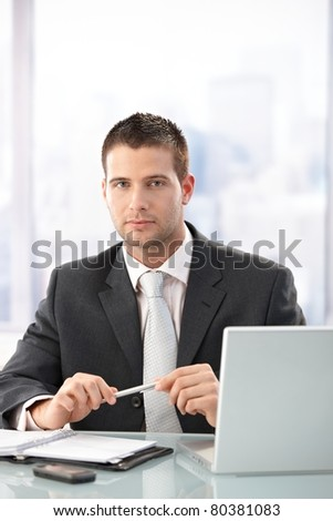 Young handsome executive sitting at desk in bright office.? - stock photo