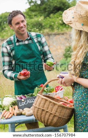 Young handsome farmer selling organic vegetables to pretty blonde at a farmers market - stock photo