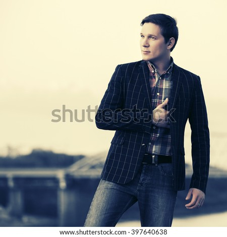 Young handsome fashion man walking outdoor - stock photo