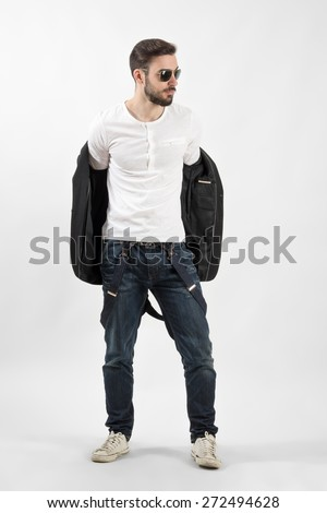 Young handsome fashion model putting on jacket. Full body length portrait over gray background.