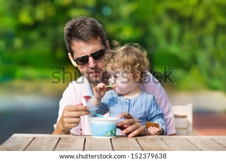 Young handsome father and his little baby daughter enjoying ice cream in the garden on a sunny autumn day - stock photo