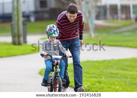 young handsome father teaching his son to ride a bike - stock photo
