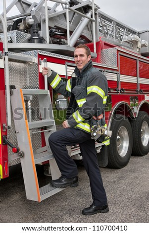 Young Handsome FireFighter standing in front fire truck portrait - stock photo