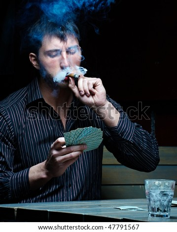 Young handsome gambler with cigar and cards