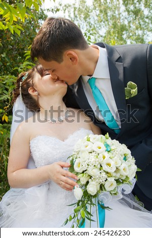 Young handsome groom in suit kissing beautiful bride while wedding - stock photo