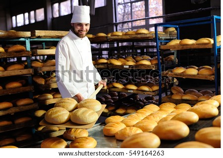 young handsome guy baker pulls out of the oven fresh bread at the bakery background