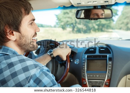 Young handsome guy driving his new car - stock photo