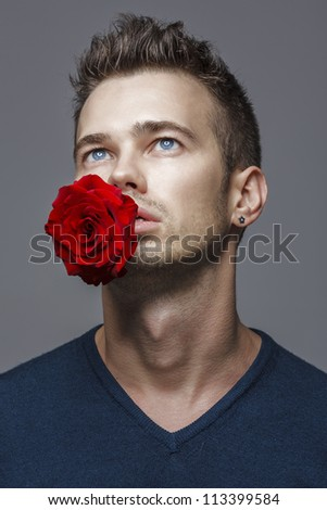 young handsome guy holding a red rose in his mouth - stock photo