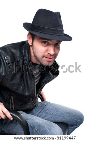 young handsome guy in a hat sitting Caucasian man in a leather jacket to a leather chair and looks attractive, isolated over white, cool smile - stock photo