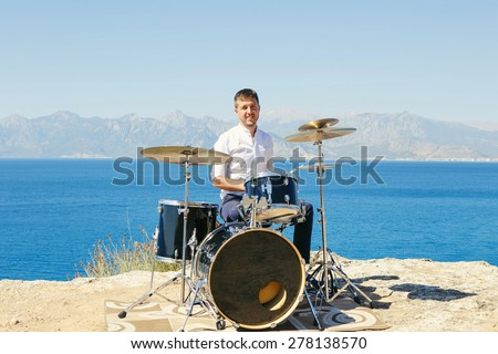 Young handsome guy in a white shirt drummer sitting behind the drum kit outdoors and unseat him the sea and beautiful sky - stock photo
