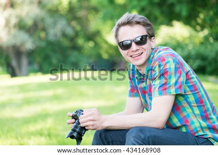 Young handsome guy in colorful shirt looking  on pictures in camera and sitting on stump in park